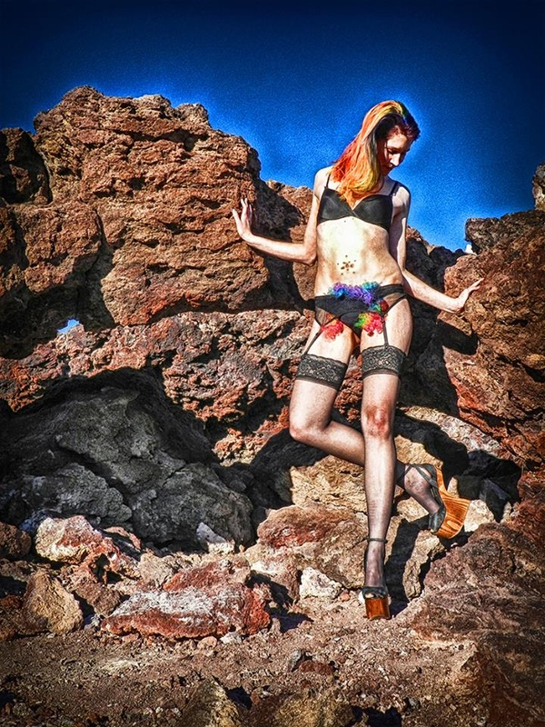 model with rainbow colored hair and rainbow clown wig on crotch against volcanic rocks