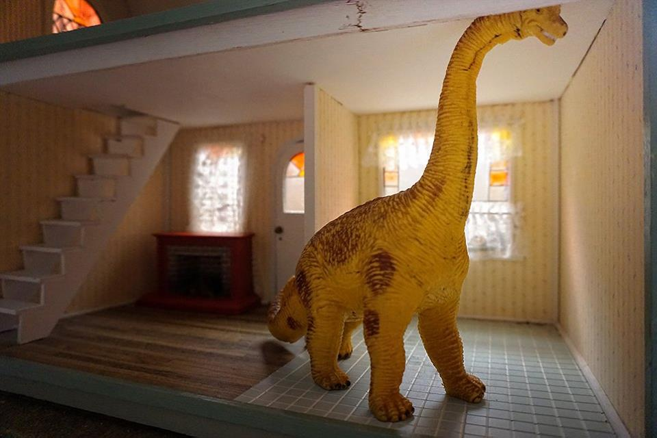 toy dinosaur in doll house