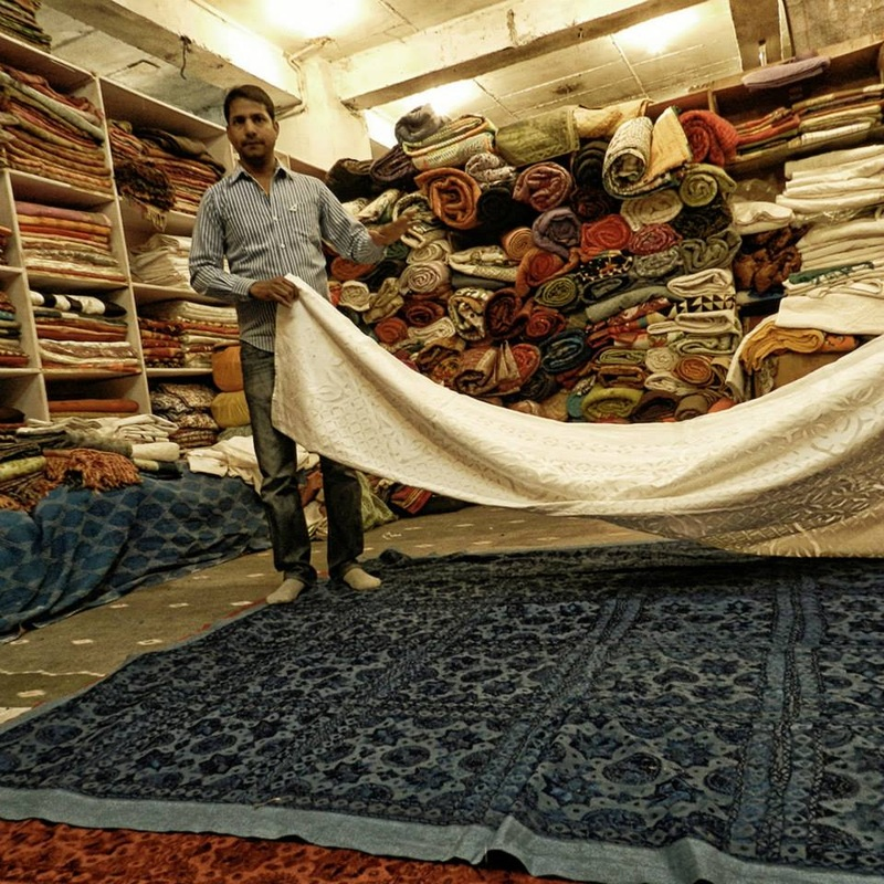 man selling textiles in basement of antique shop