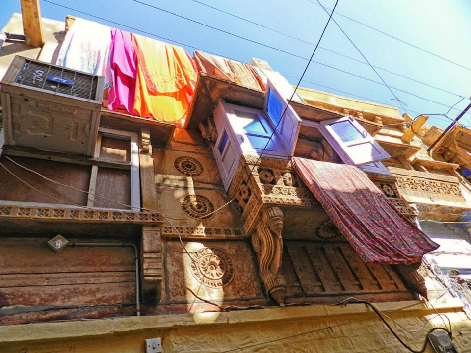 colorful laundry hangs by blue window