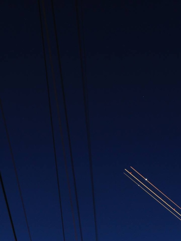 nighttime sky with powerlines and airplane lights