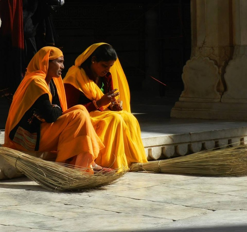 women in orange saris taking a break from sweeping with grass brooms