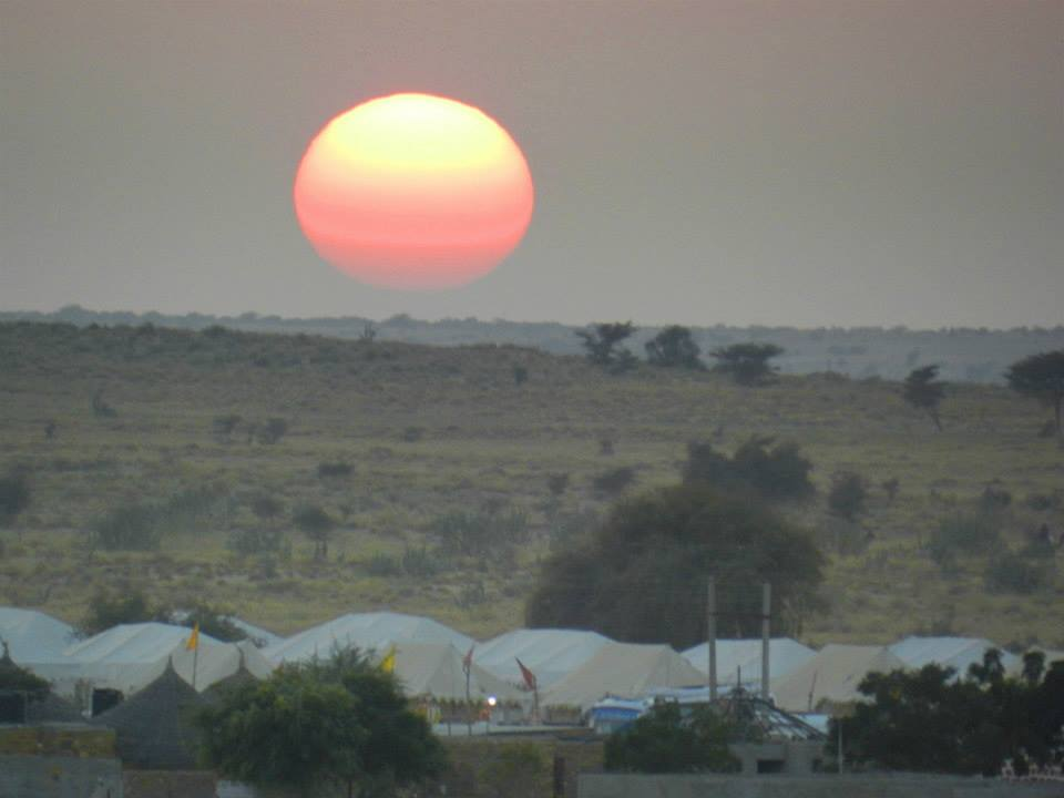 red sun setting over desert