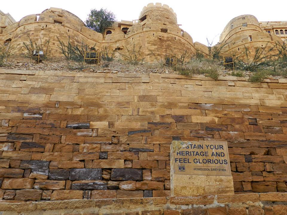 broken stone sign at foundation of Jaisalmer fort reads