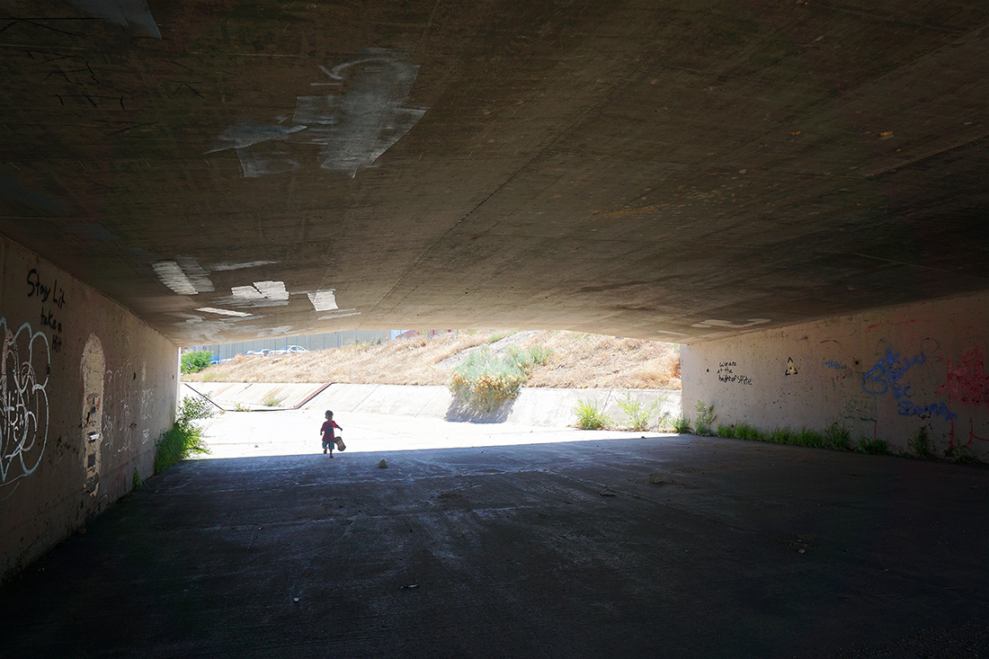 child under bridge