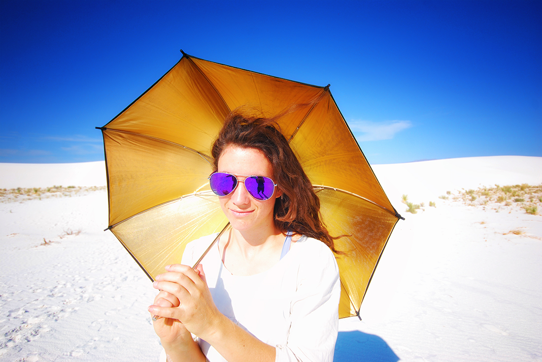 portrait of woman with purple glasses and gold umbrella in white sands national monument