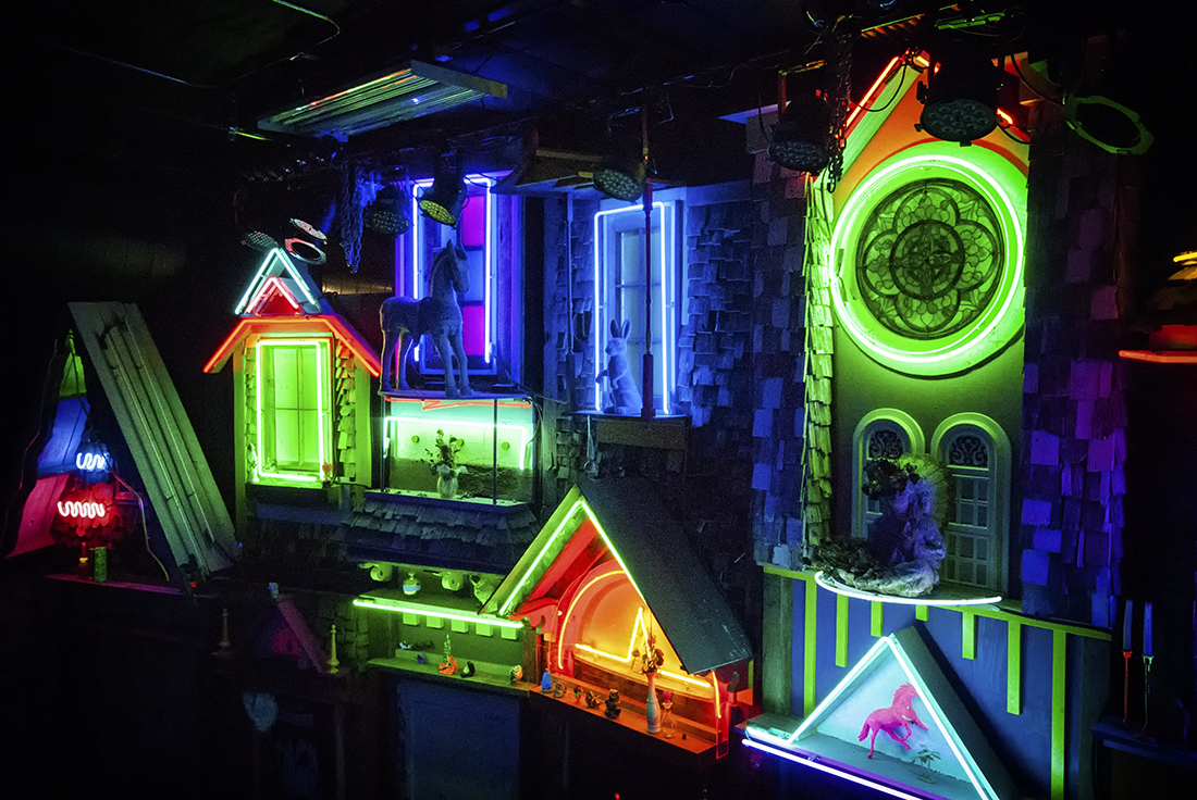 neon housing development with toys at meow wolf