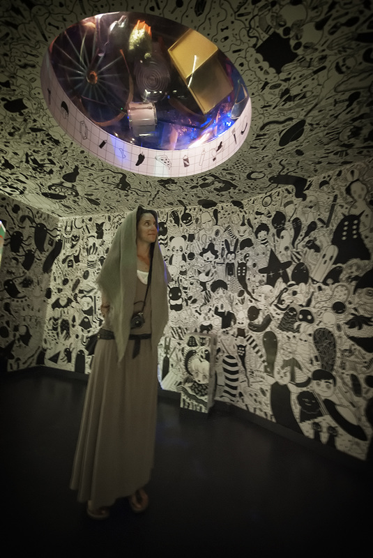 woman stands under portal window meow wolf