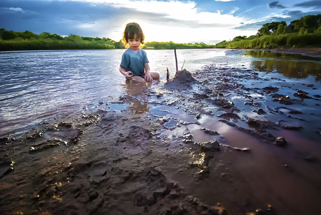 child plays in water and mud in river at sunset