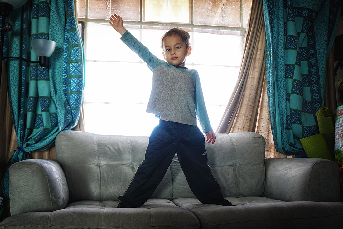 boy poses on couch in front of window