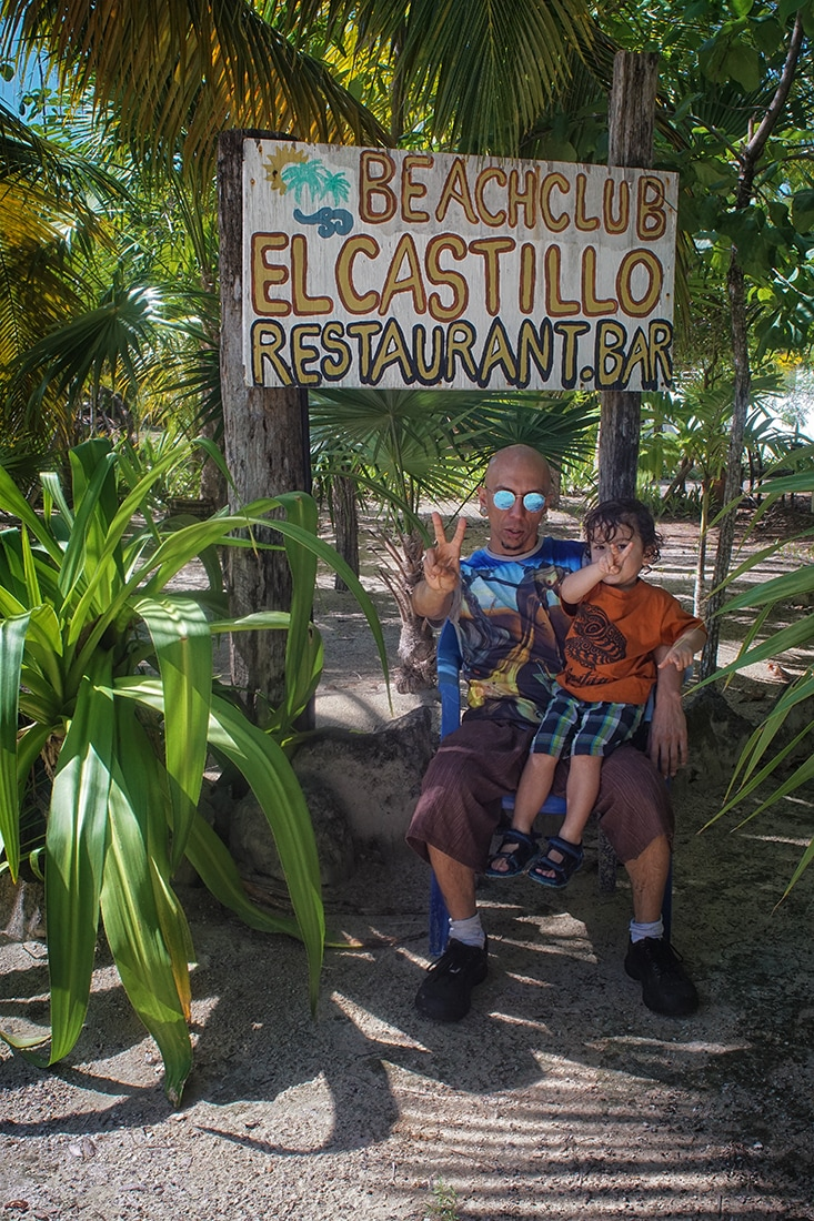 father and son under El Castillo Beach Club sign, Costa Maya