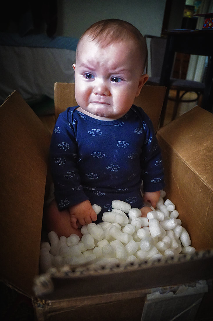 sad face baby in box of styrofoam peanuts