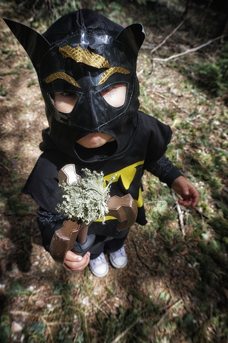 child in Batman costume holds lichen on grappling hook