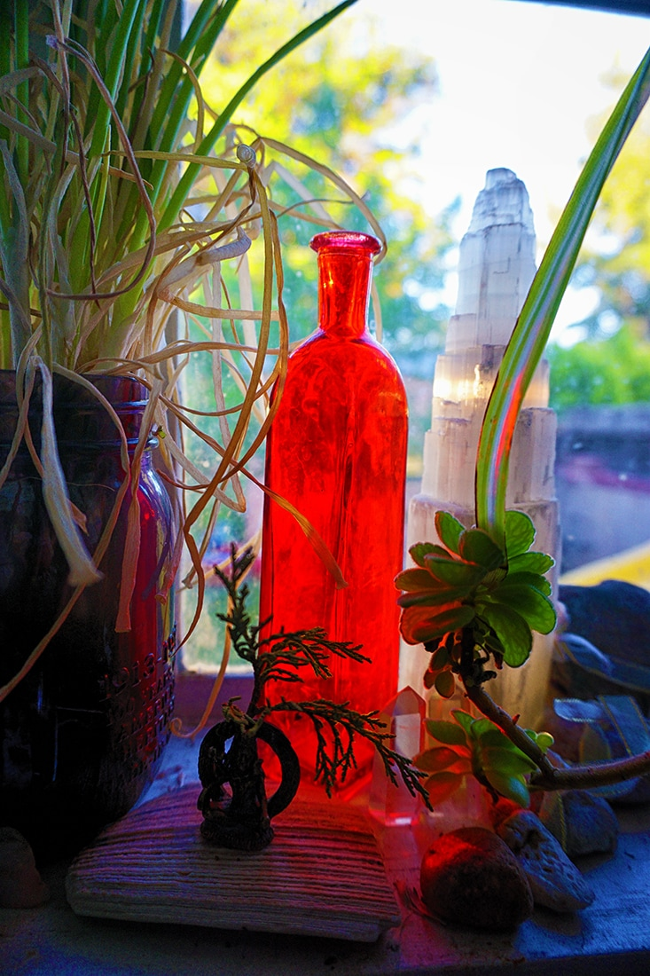 red glass jar illuminated on windowsill