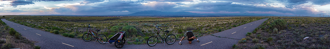 Panoramic on bike trail with man stretching