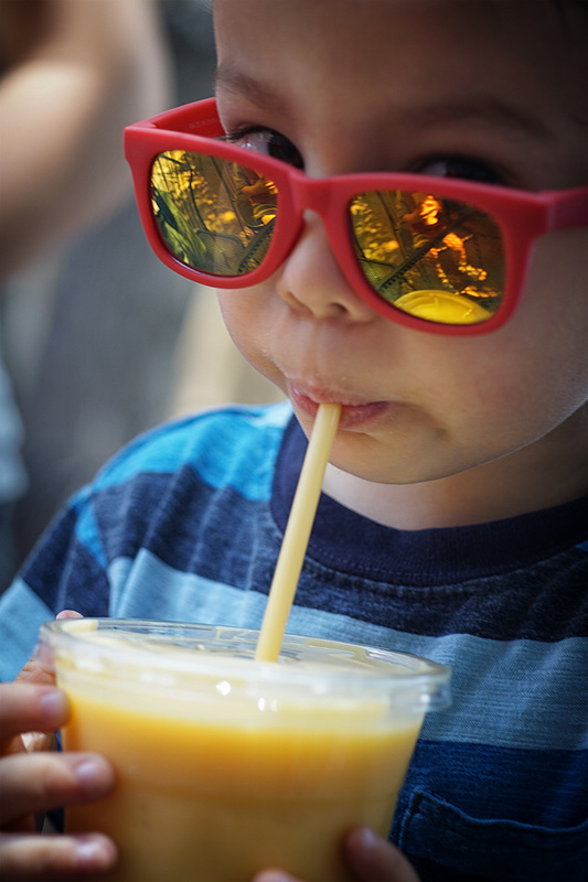 child wears sunglasses and drinks mango lassi