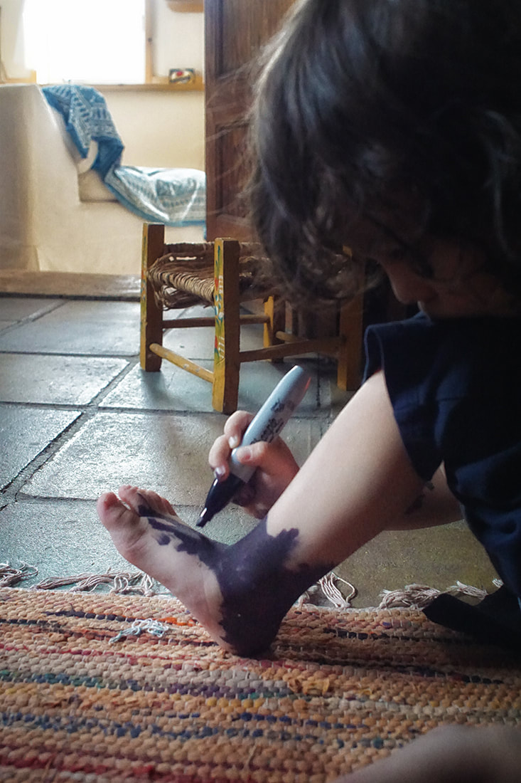 boy colors foot with sharpie marker -