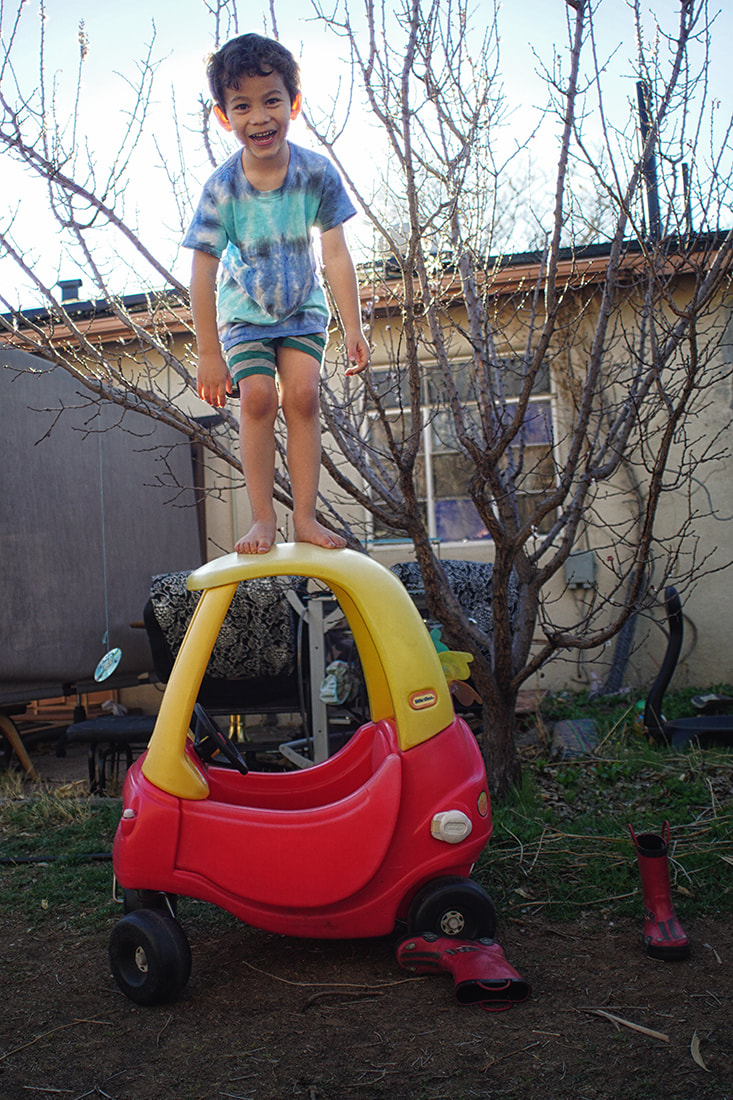 boy stands on play car