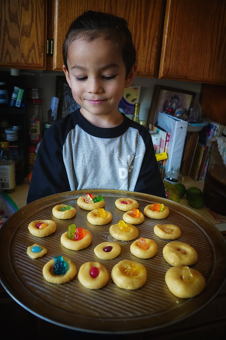 boy holds shortbread and gummy bear cookies he baked