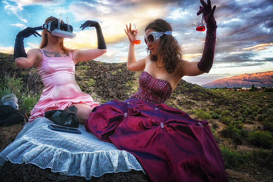 women in ballroom gowns wearing goggles and holding colorful beakers in the desert