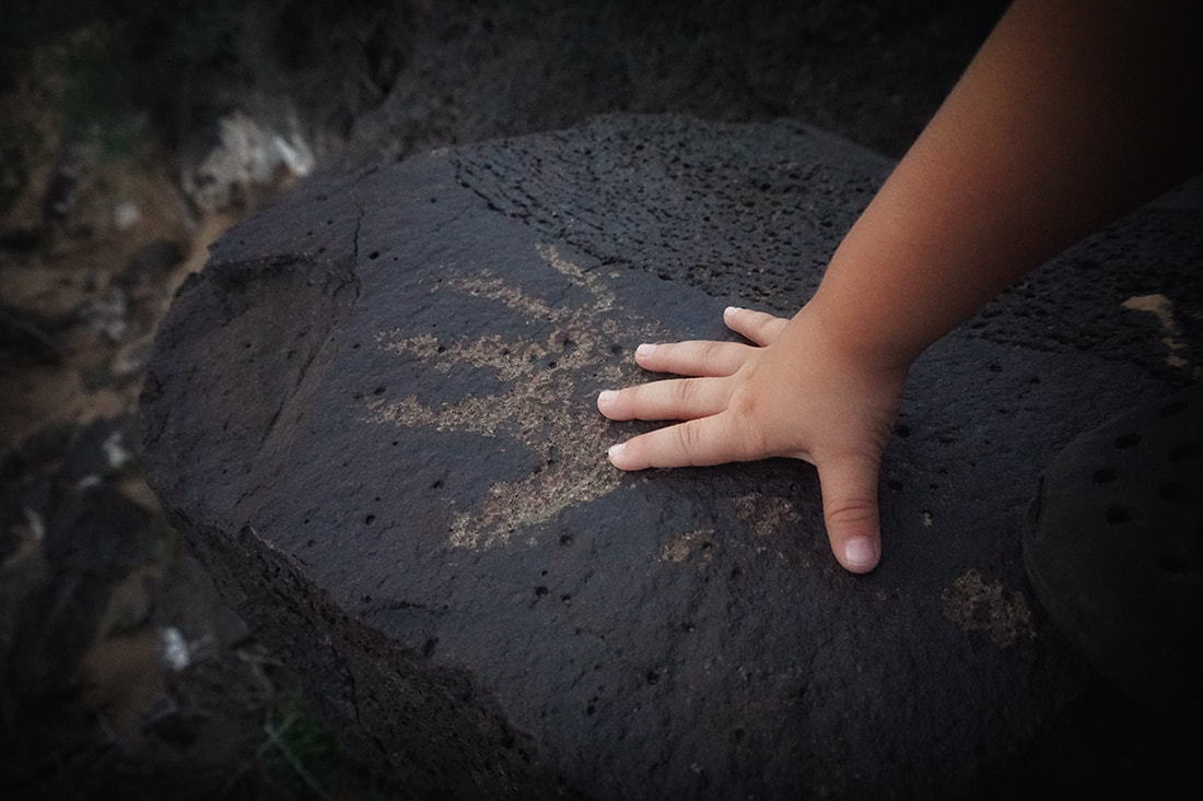 child puts hand by petroglyph of handprint