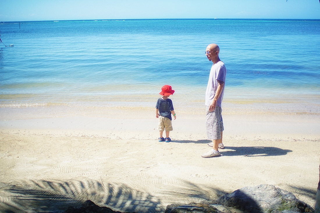 father and son on beach roatan honduras