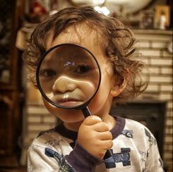 the child looks through a magnifying glass (and squishes his face)