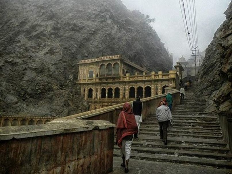 people walking up stairway leading into the Monkey temple in the mountains