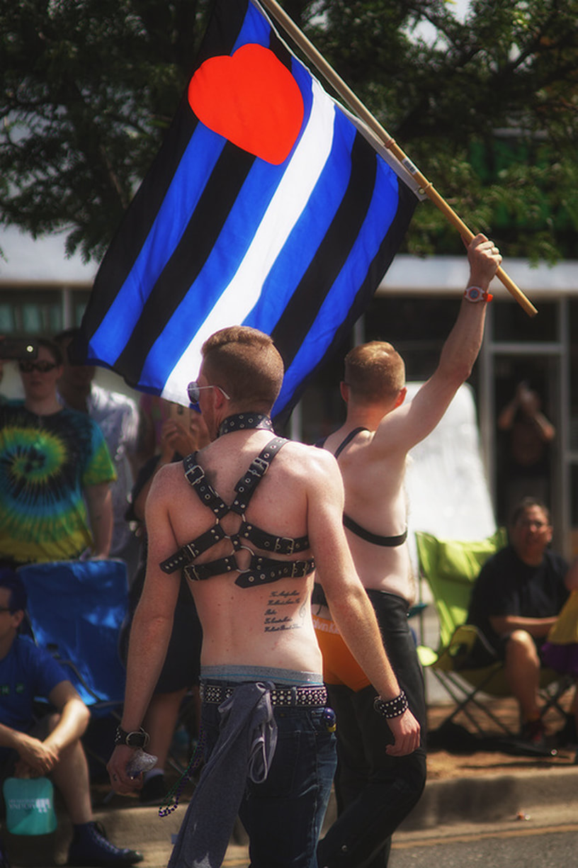 men in bondage gear with heart flag