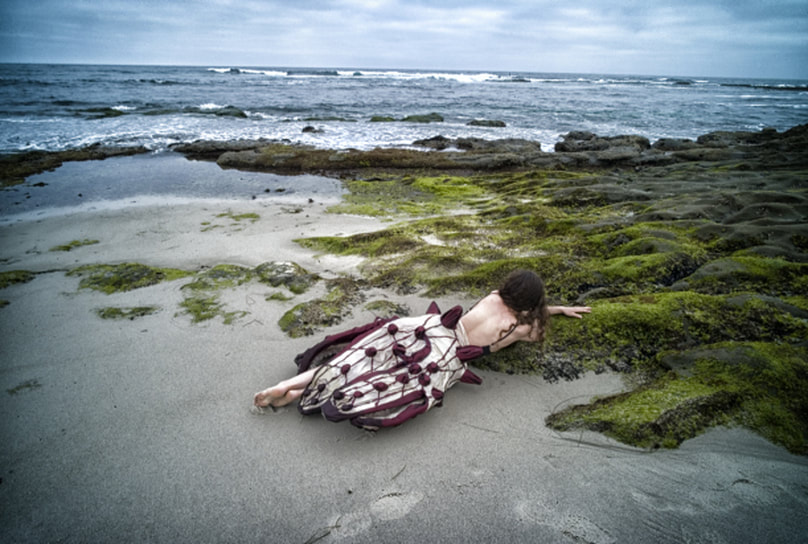 Woman in starfish skirt Lying amongst the rocks covered with sea moss.