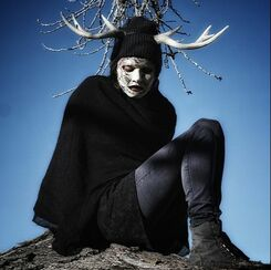 woman with antlers and mask sits on tree