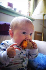 baby eats sweet potato