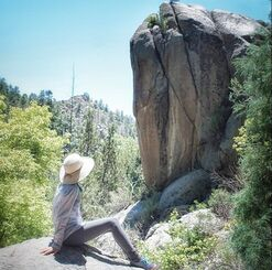 woman on boulder looking at rock outcrop