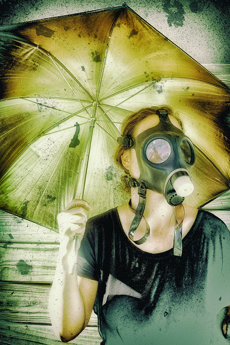 apocalyptic self-portrait woman with golden flash reflector umbrella and gas mask