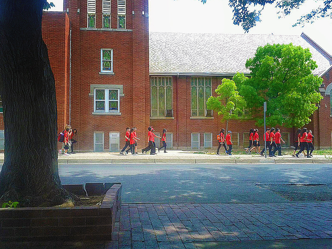 group of school children in uniform walk by church