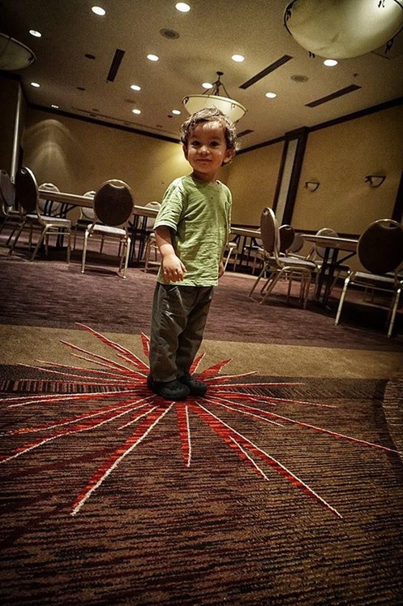 boy in ballroom stands on red carpet pattern