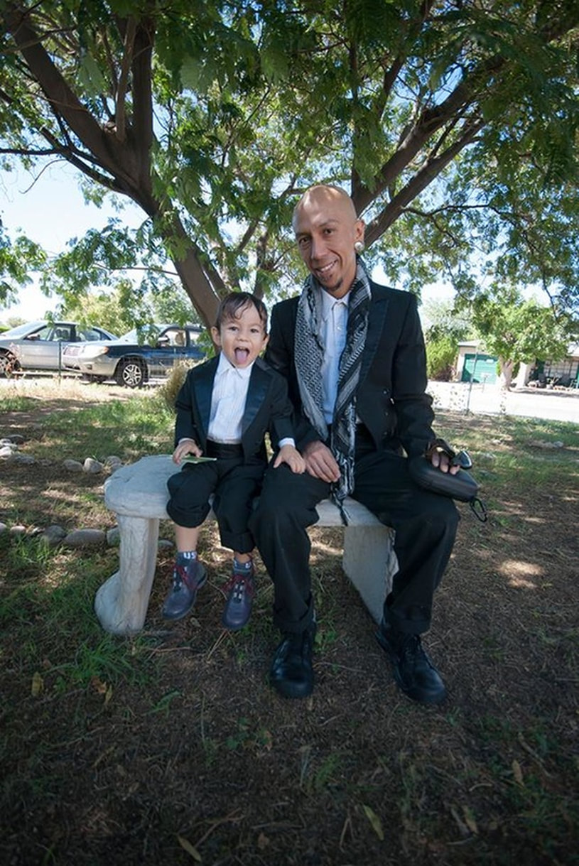 father and son sit on bench in wedding attire