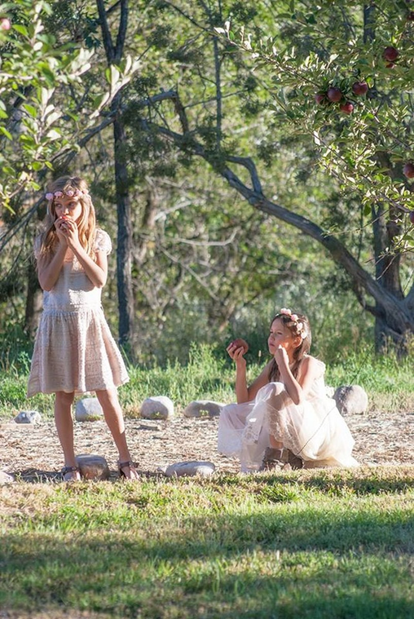 girls in flower girl outfits eat apples at wedding