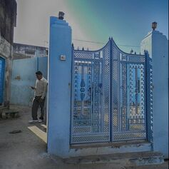 guide looks at cell phone while leaning against blue wall with ornate gate