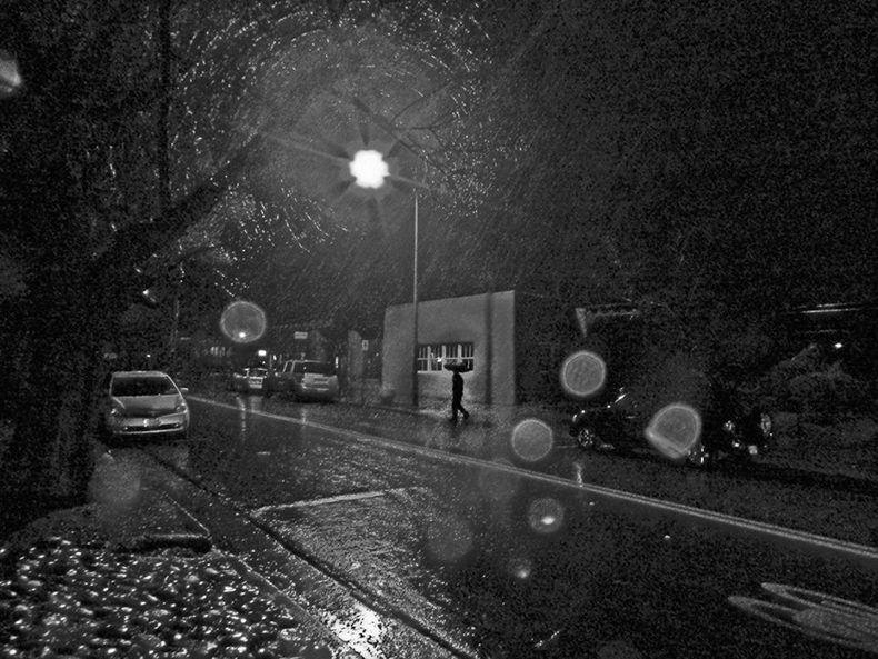 person walking down the street in the rain with umbrella under streetlight