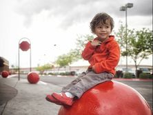 boy sits on red ball