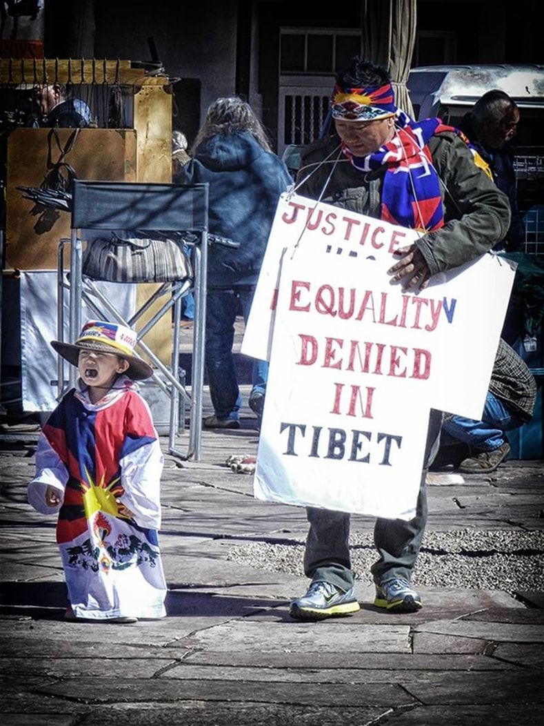 Tibetan man and crying child at demonstration