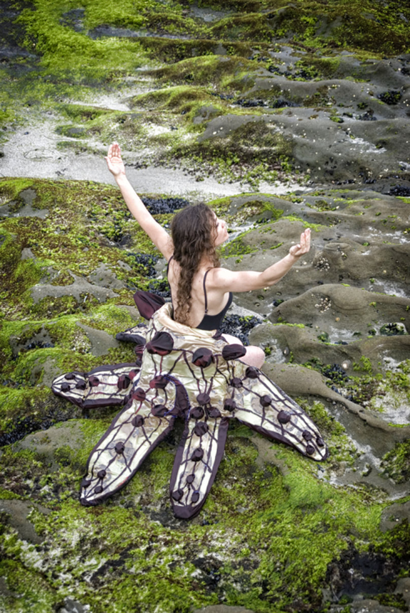 woman in starfish skirt on rocks
