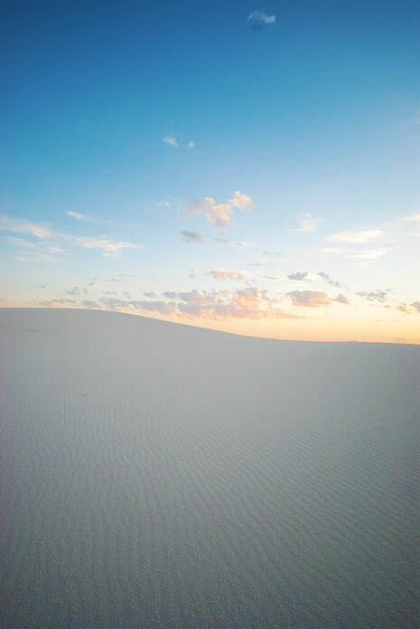 white gypsum dunes and clouds at sunrise