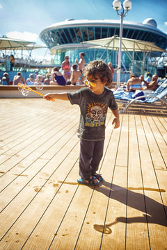 boy blowing bubbles on top deck of cruise ship