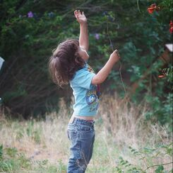 child reaches for branch of flowers