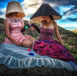 women in ballroom gowns wearing lampshade hats and toasting colorful beakers in the desert