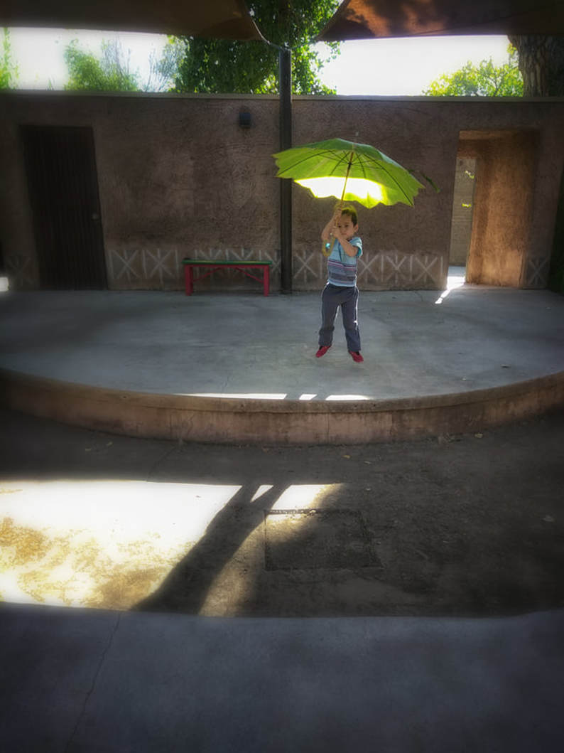 kid jumping with umbrella